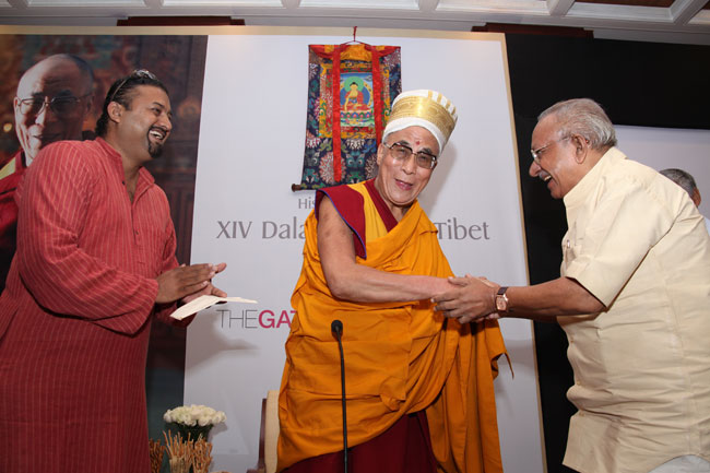 Cartoonist Yesudasan presents a 'Kerala Thalappavu' (headgear) to His Holiness the XIV Dalai Lama of Tibet during a Friends of Tibet private audience at The Gateway Hotel of Taj, Kochi on September 04, 2010.
